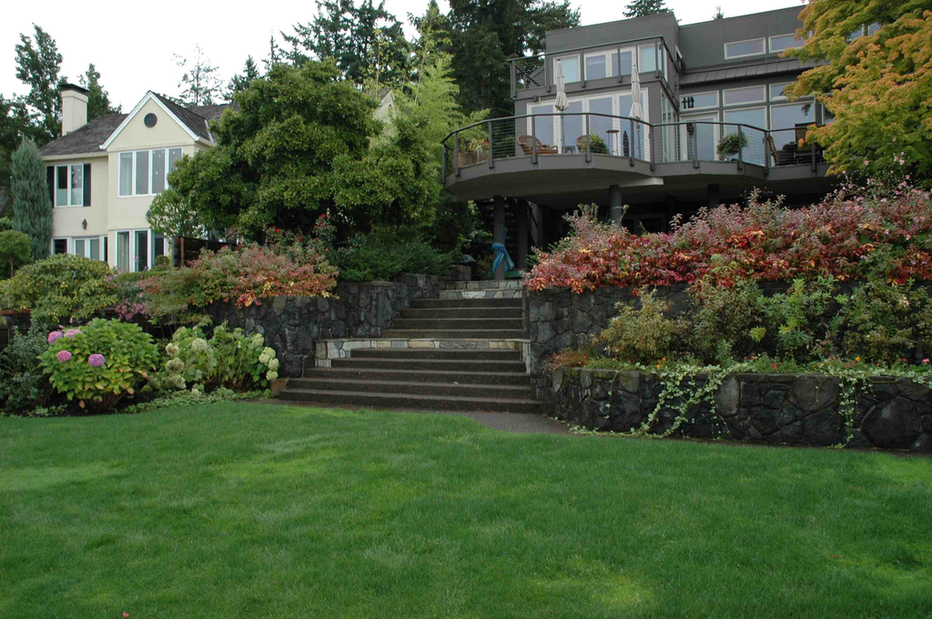 Located in Lake Oswego, this project features a front yard made of a deep-shade garden with walls of reclaimed stone and gravel paths.