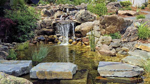 The Garden Artist created a waterfall that spills into a fishpond, which is flanked by a walkway of stones that appear to float above the water.