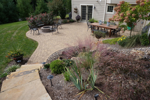 At the end of the curved stairs made of stone, lies a patio built of pavers also featuring a firepit.
