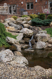 Water features are a staple in the Virginia area, including this waterfall constructed with natural boulders flowing into a koi pond.