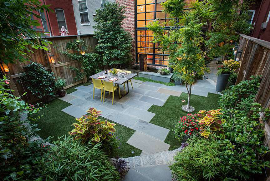 This small backyard is able to pack in greenery, hardscaping, and seating in 22' by 22' area. Photo: Botanical Decorators