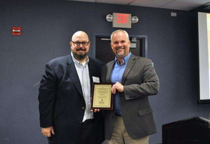 STIHL's corporate communications manager, Roger Phelps, accepts award from NRHA Vice President of Publishing Dan Tratensek.