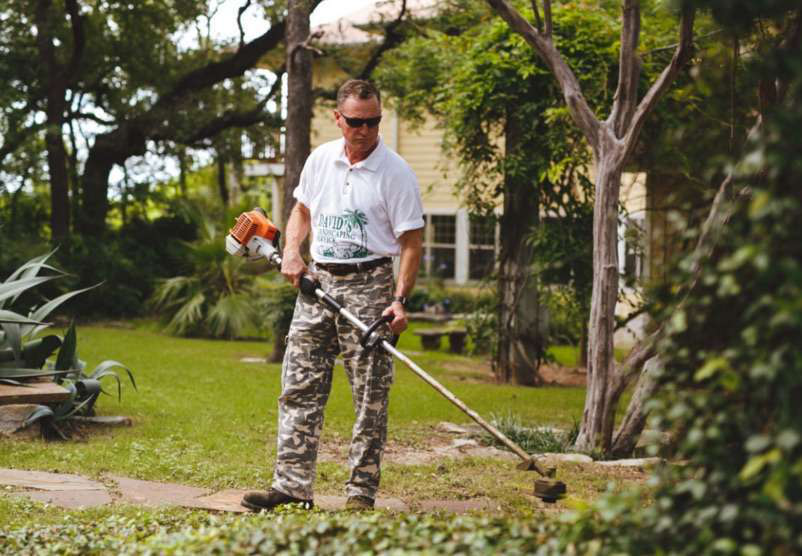 Landscape Professional Weed Eating Grass Lawn
