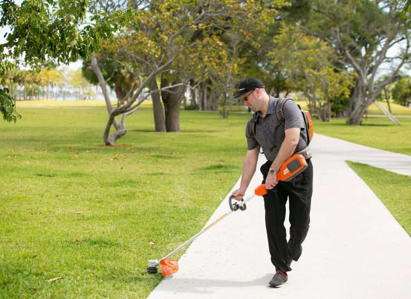 man with electric mower by husqvarna
