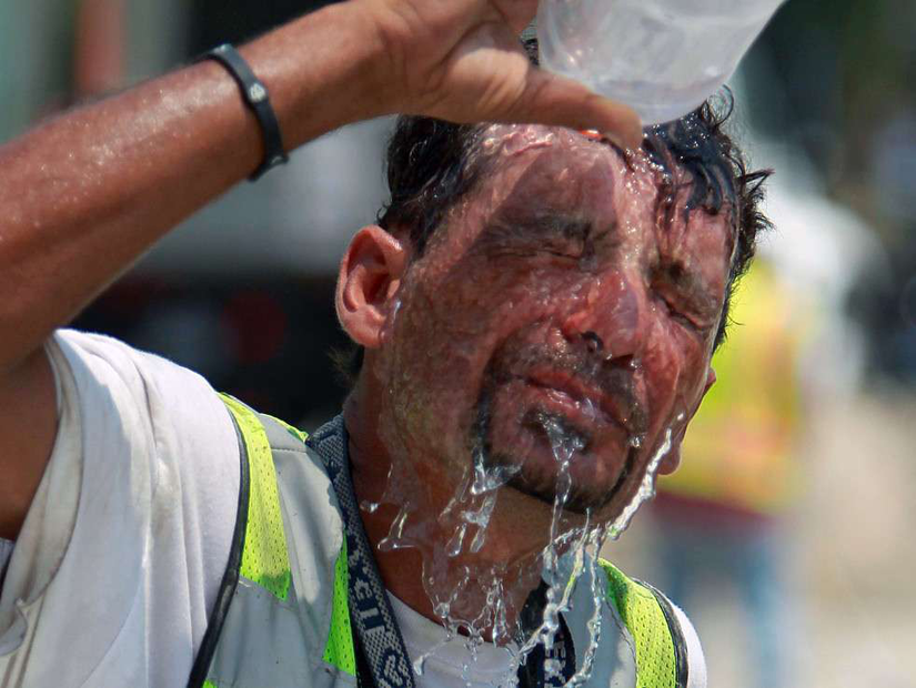 worker tries to stay hydrated and keep cool in the summer heat