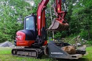 blade buddy attachment on kubota carrying boulder