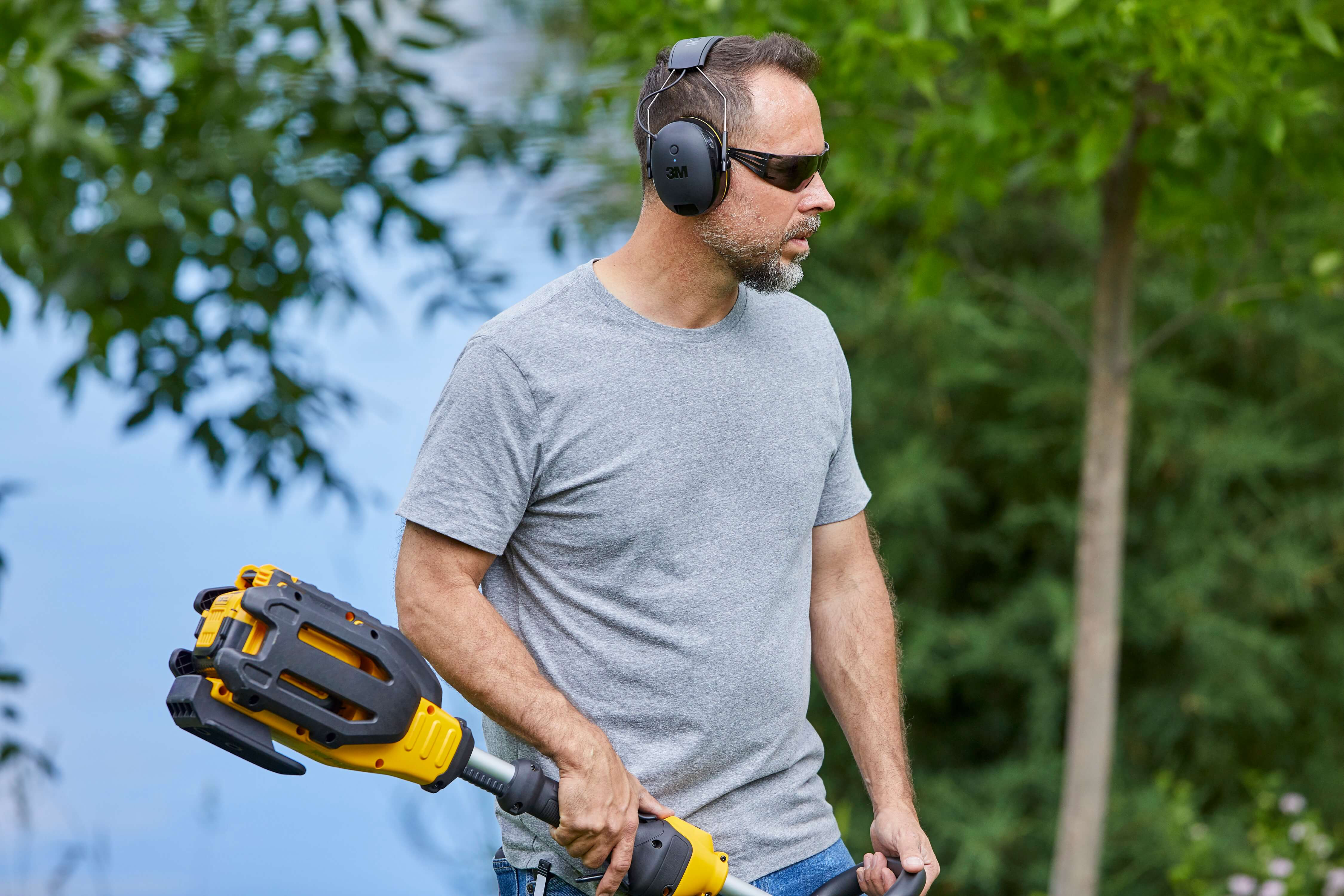 man in safety gear with weed trimmer