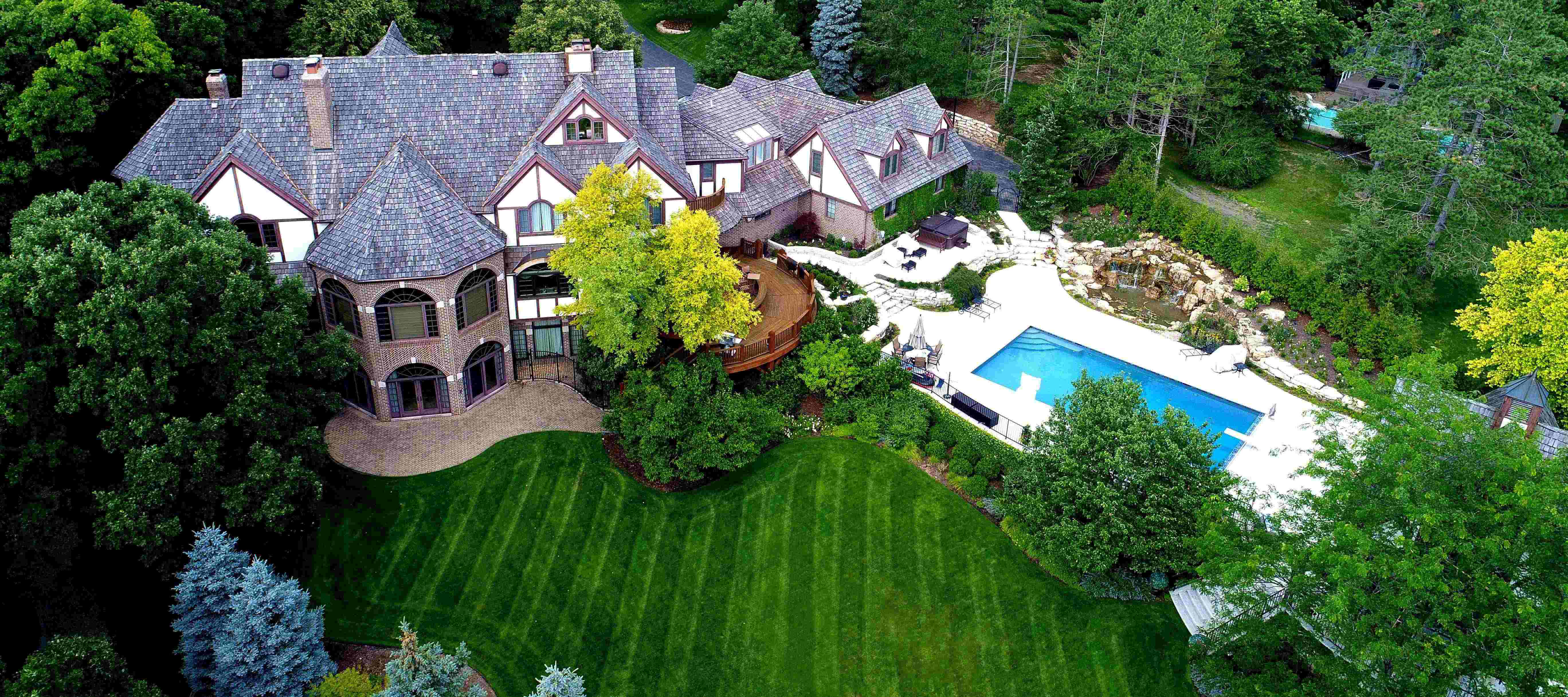 mansion with landscaped lawn and pool