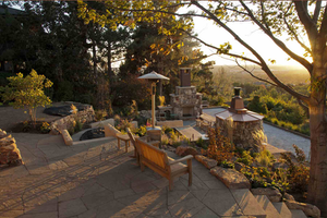 Stone Patio surrounded by trees with sun setting