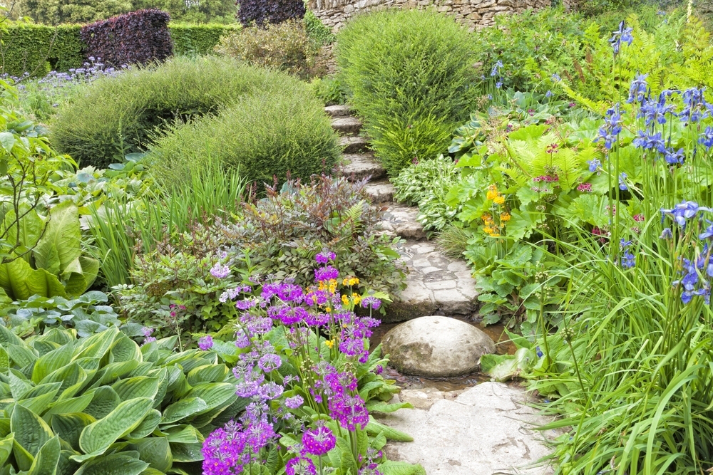photo of a colorful garden with a stepping stone path through the center on a sunny day