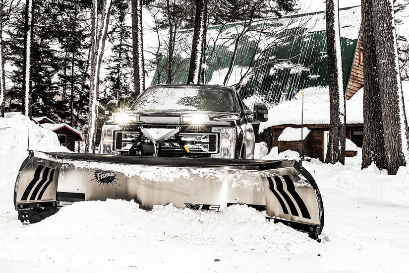 Truck with snow plow attachment in the snow