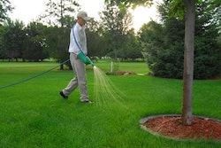 A landscaper spraying herbicide on a lawn