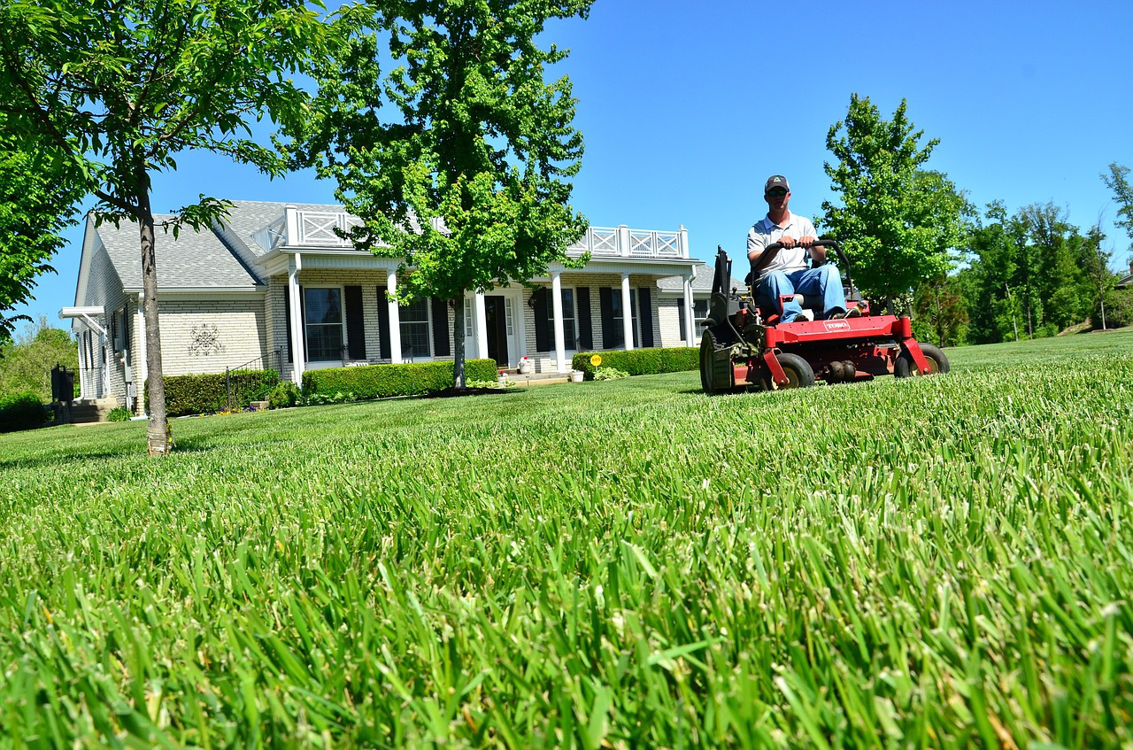 landscaper on riding lawn mower cutting grass in the front yard