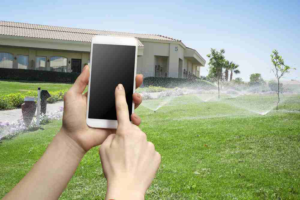 Mobile phone with lawn and sprinkler system in the background