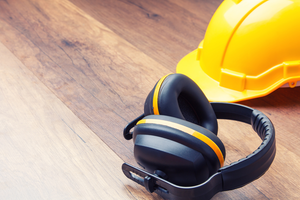 A yellow hard hat and hearing protection on hardwood floor
