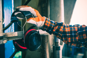 A worker's gloved hand reaching for a pair of safety earmuffs