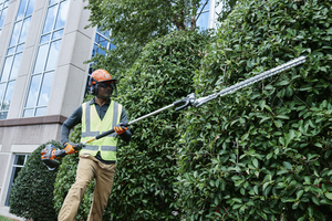landscaping professional using husqvarna hedge trimmer