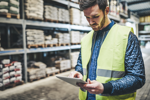man in a warehouse wearing a safety vest and looking at a tablet