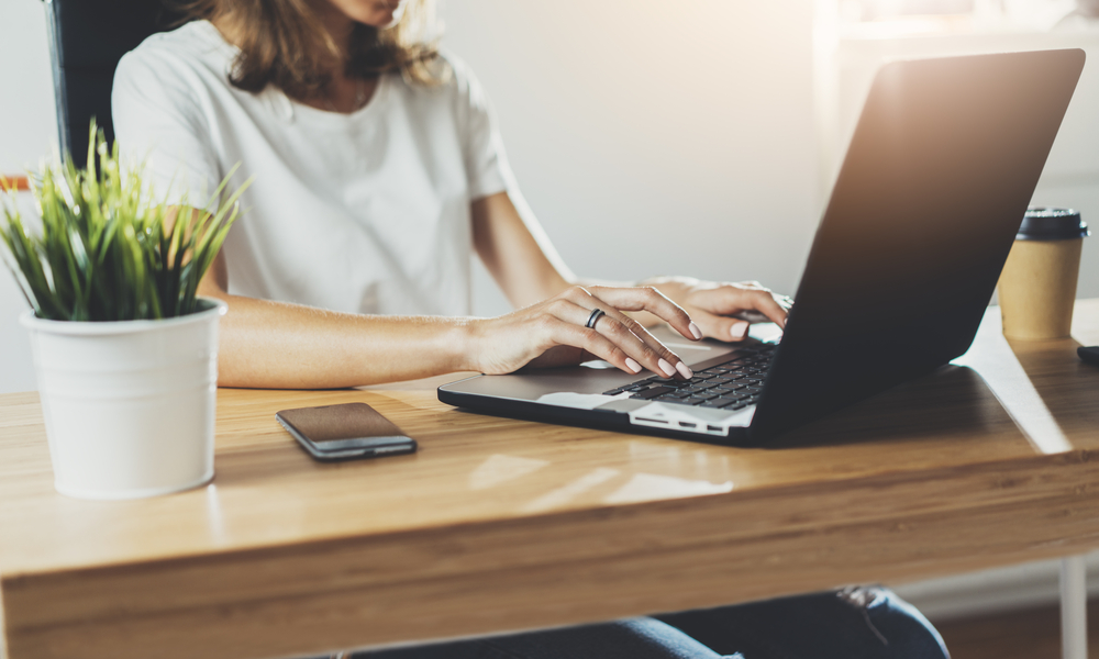 woman sits at desk with laptop, phone, coffee, and desk plant