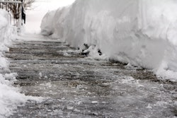 An icy sidewalk with snow mounds on either side