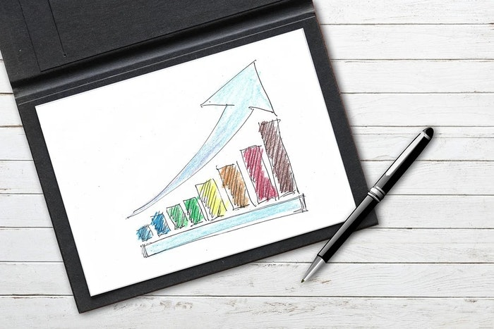 a colorful upward trending bar graph on paper with a pen
