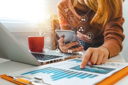 Social and technology icons stemming from a phone while a person points at graphs beside an open laptop