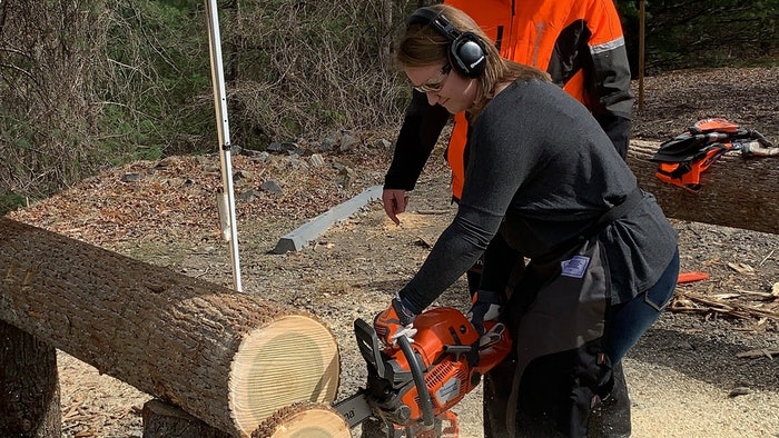 Beth Presley using a chainsaw to cut a log into slices