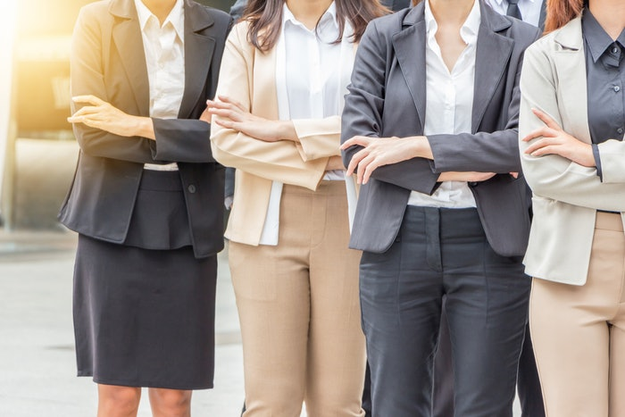 Four businesswomen standing with their arms crossed