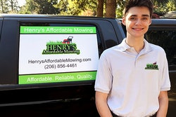 henry standing next to signage on a truck advertising his affordable lawn mowing services