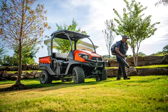 Kubota's gas-powered RTV520 utility vehicle next to a landscaper clearing leaves with a backpack blower