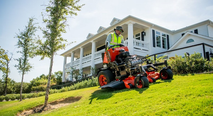 A landscaper cutting grass with a Kubota SZ Series commercial stand-on mower