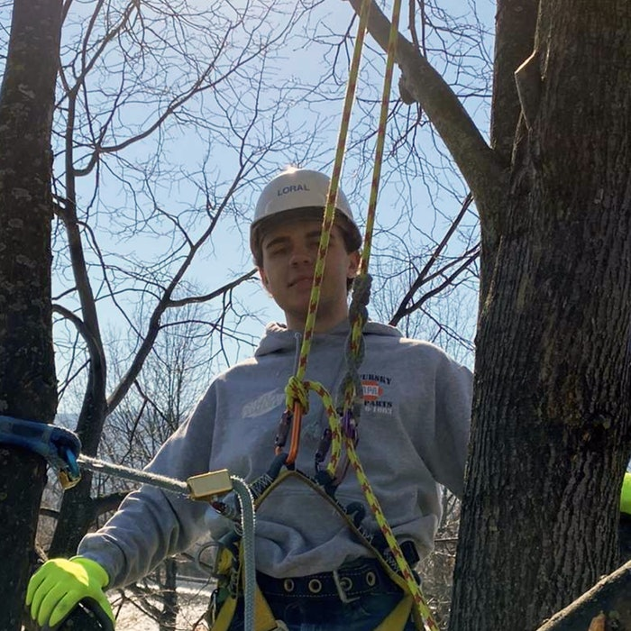 Ruppert Landscape Company Scholarship winner Nick Bianchi wearing protective gear while harnessed in a tree