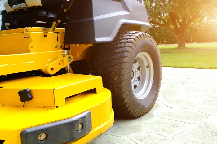 A yellow riding lawn mower parked on a driveway