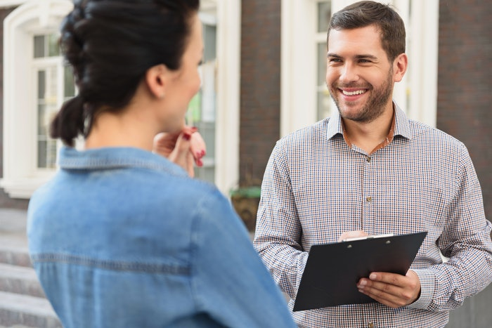 Man with clipboard speaking to woman