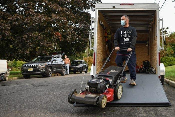 man unloading lawn mower off landscaping truck