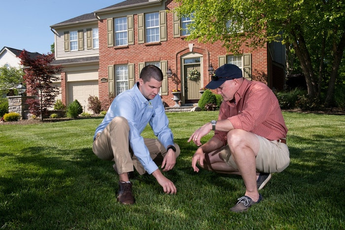 Landscape professional and client discussing the grass on front lawn