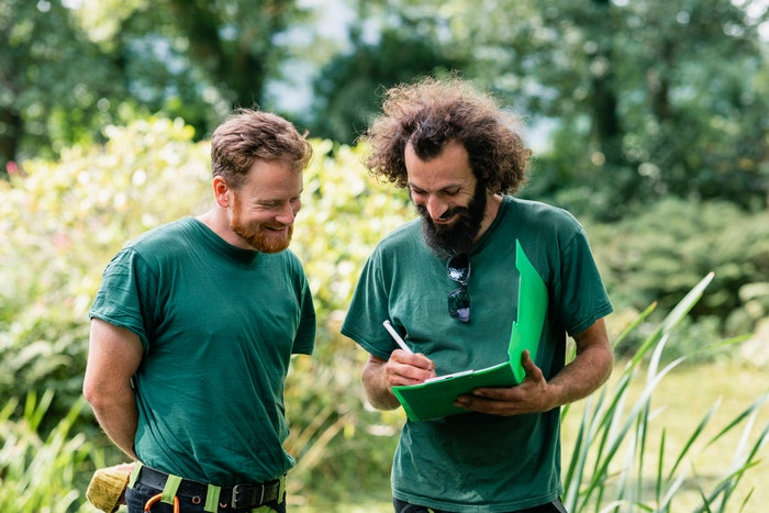 two men discussing paperwork in a yard