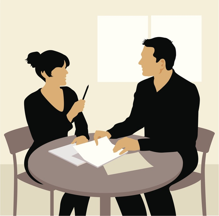 man and woman at desk discussing paperwork