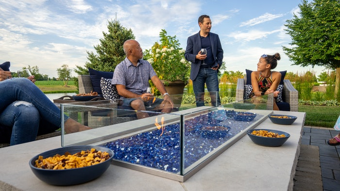 group of people sitting around an outdoor fire pit patio area