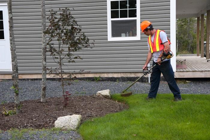 landscaper wearing orange safety vest and hat while edging a yard
