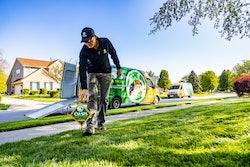 lawn care technician placing sign green lawn.jpg